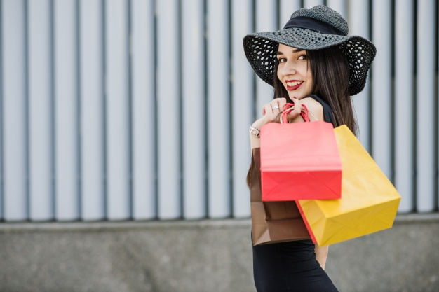 Girl with shopping bags posing outside