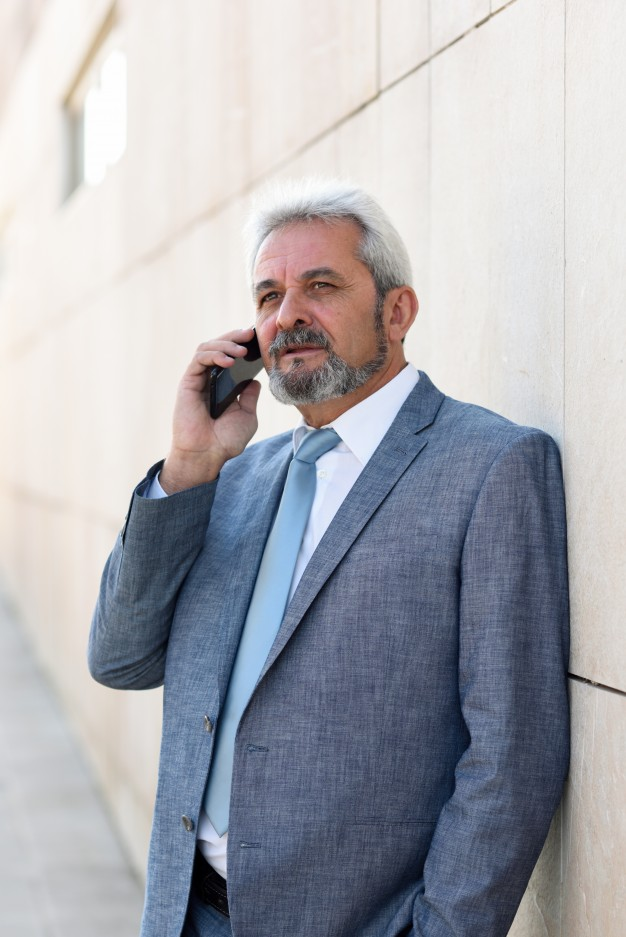 Senior businessman with smartphone outside of modern office building.